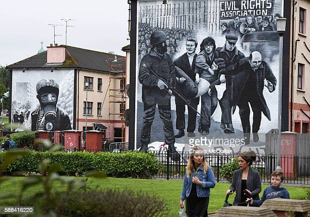 A family walks past a mural depicting a scene from Bloody Sunday as final preparations for the funeral of the late retired Bishop of Derry Dr Edward...