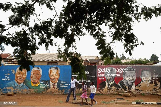 A family walks past a mural depicting former South African President Nelson Mandela during different times in his life near the Regina Mundi Catholic...
