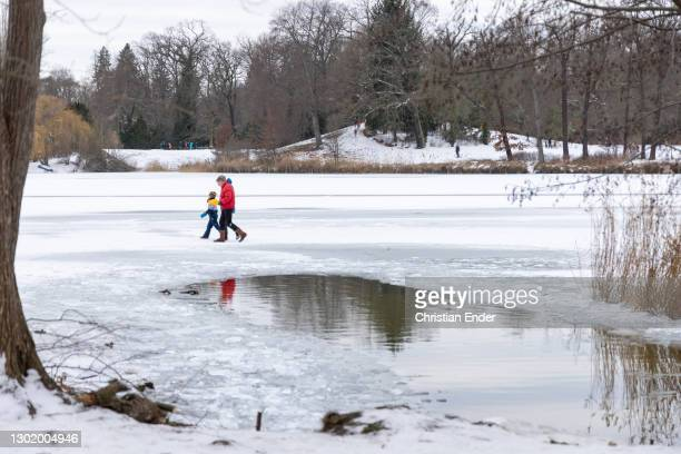 Family walks past a thawed portion of the ice-covered Heilige See lake on February 13, 2021 in Potsdam, Germany. A recent snowstorm dumped snow...