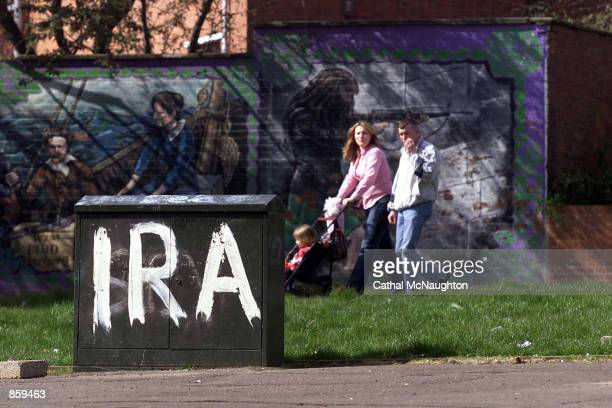 Family walks past Irish Republican Army graffiti April 8, 2002 in Belfast, Northern Ireland. Sinn Fein president Gerry Adams and decommissioning...