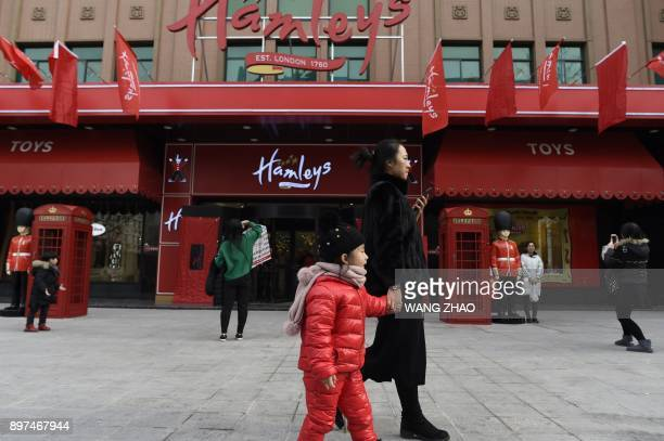 A family walks past on the opening day of a new Hamleys store the iconic British toy retailer now Chineseowned in Beijing on December 23 2017 The...