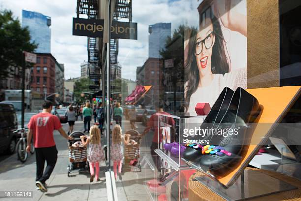 A family walks past shoes on display in the window of a Crocs Inc store in the shopping district of Soho in New York US on Saturday Sept 14 2013...