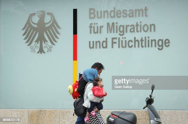 A family walks past the Berlin office of the Federal Agency for Migration and Refugees also known as BAMF on May 18 2018 in Berlin Germany German...