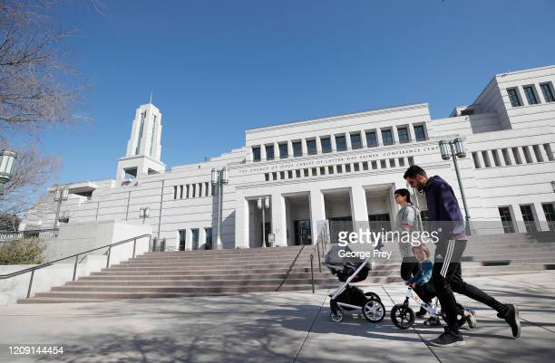 A family walks past the grounds of the Conference Center that sits empty for the 190th Annual General Conference of the Church of Jesus Christ of...