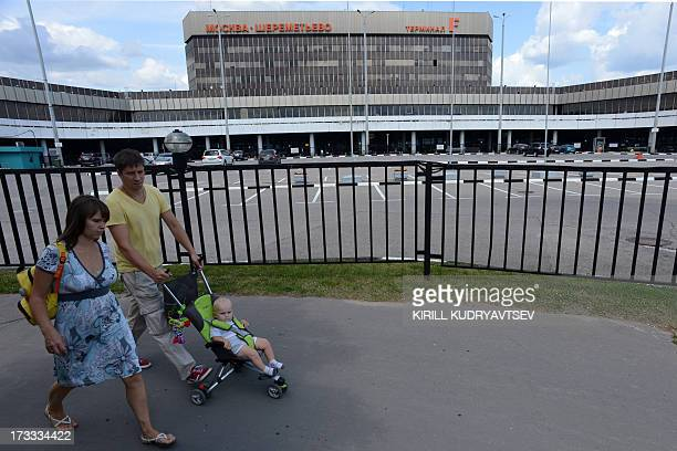 A family walks past the terminal F of Moscow's Sheremetyevo airport on July 12 where US National Security Agency fugitive leaker Edward Snowden...