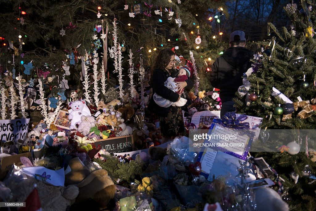 A family walks through a makeshift memorial in the Sandy Hook village center December 20, 2012 in Newtown, Connecticut. People continue to mourn the killing of 20 students and 6 adults by ALLEGEDgunman Adam Lanza at Sandy Hook Elementary School last Friday. AFP PHOTO/Brendan SMIALOWSKI
