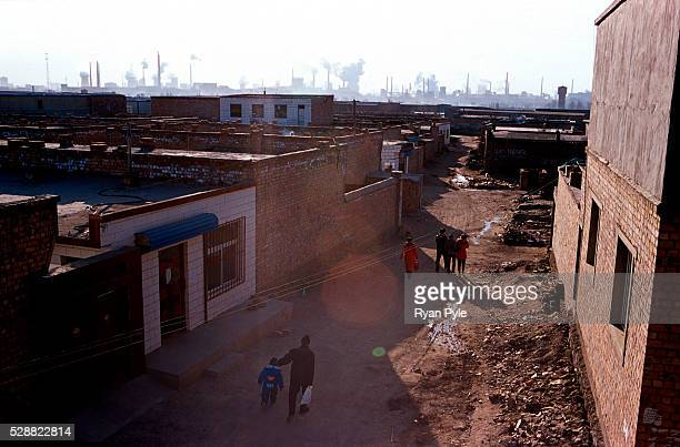 A family walks through a small neighborhood near the Bao Steel mill in Baotou Inner Mongolia China Baotou is an excellent example of a oneindustry...