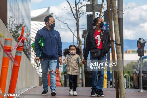Family walks wearing masks in Downtown Los Angeles on March 22 during the coronavirus outbreak. - The US president on March 22 said he had ordered...