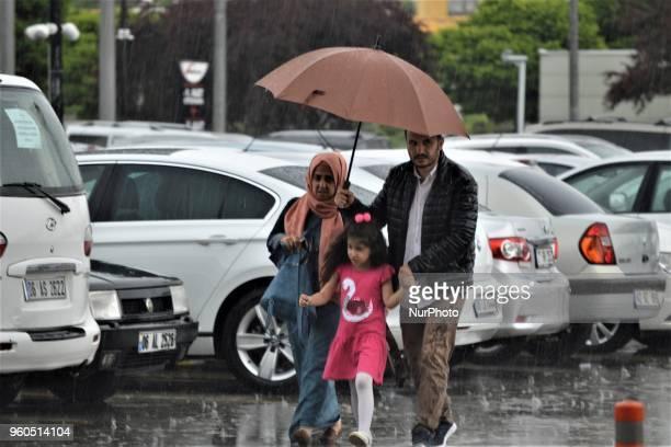 A family walks with an umbrella outside a shopping mall in Ankara Turkey on Sunday May 20 2018