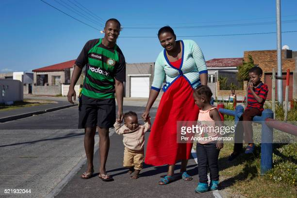 A family walks with their children close to a playground in Guguletu a township about ten miles outside Cape Town South Africa