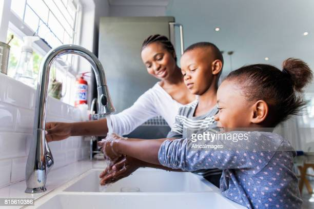 Family washing their hands together.