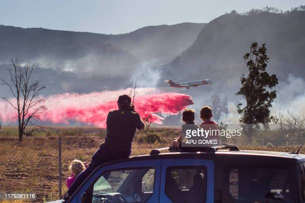 A family watches an Air Tanker dropping fire retardant over lines while helping to fight the Maria fire in Santa Paula Ventura County in California...