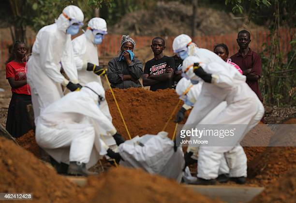 A family watches as a burial team lowers their loved one into a grave at the USbuilt cemetery for safe burials on January 27 2015 in Disco Hill...