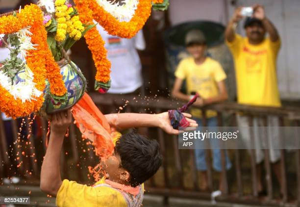 A family watches as a devotee of Hindu God Lord Krishna breaks a 'dahihandi' during a contest in Mumbai on August 24 as part of celebrations of...