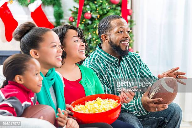 Family watches football game at Christmastime