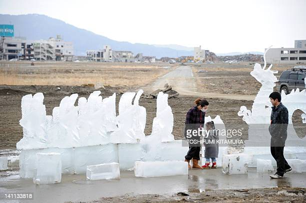 A family watches the ice sculptures in Rikuzentakata city Iwate prefecture on March 11 2012 Japan fell silent to honour the 19000 people killed...