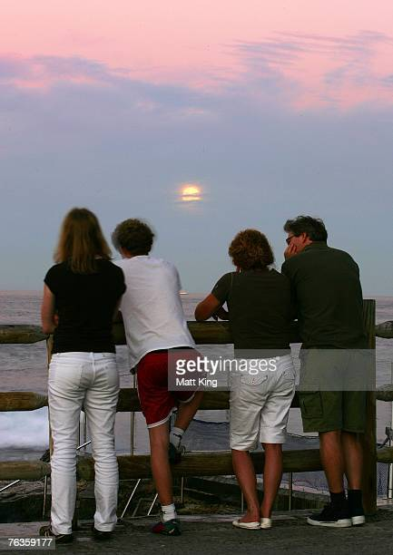A family watches the moon rise before it enters a total lunar eclipse August 28 2007 in Sydney Australia The next total lunar eclipse will not occur...
