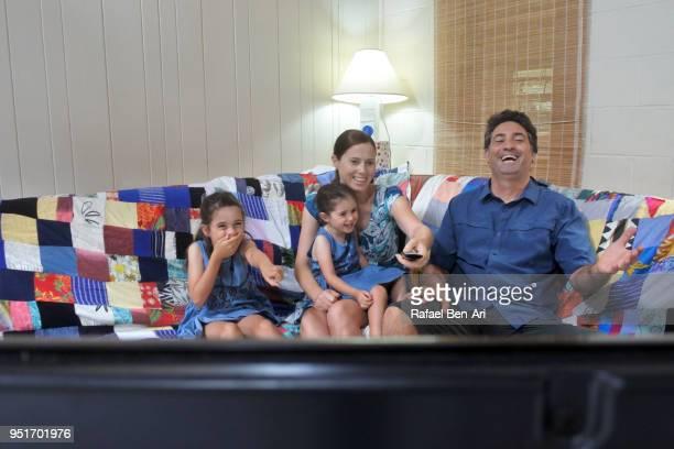 family watches tv together at home - rafael ben ari fotografías e imágenes de stock