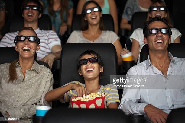 Family watching 3-D movie in theater