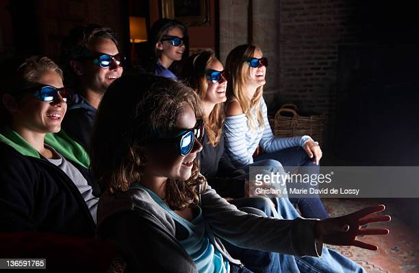 Family watching 3D television on sofa
