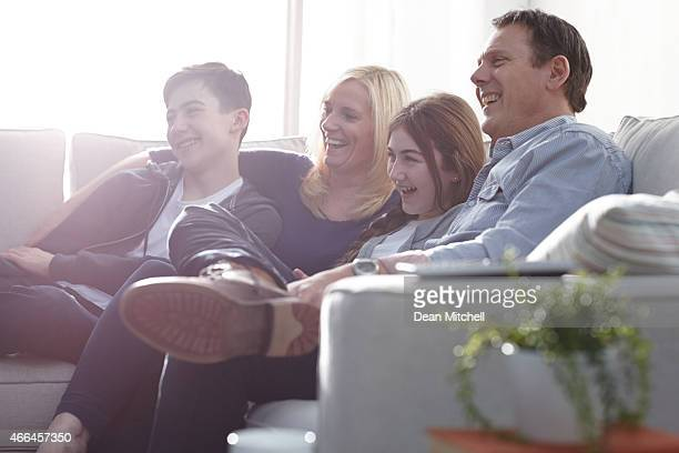 Family watching a comedy show on television