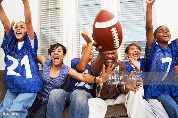 family watching a football game - sports jersey stock pictures, royalty-free photos & images