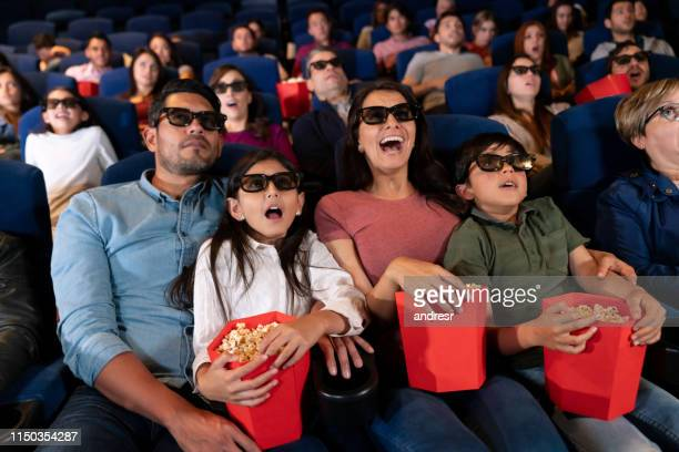 family watching a scary movie in 3d at the cinema - 3d mom son stock photos and pictures