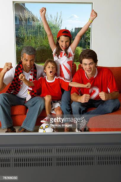 Family watching a sports match on TV.