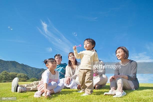 Family Watching Boy Blowing Soap Bubbles