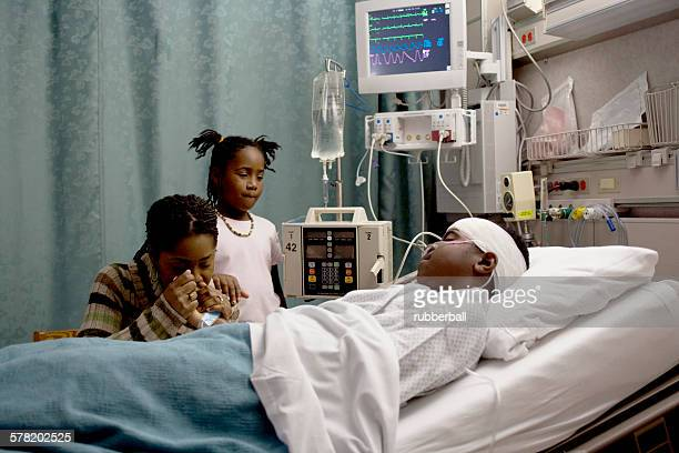 family watching boy in hospital bed with head bandages - patients brothers stock pictures, royalty-free photos & images