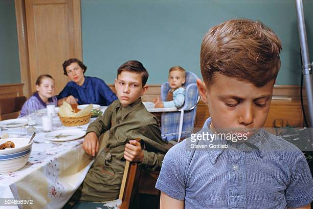 Family Watching Boy Leave Dinner Table