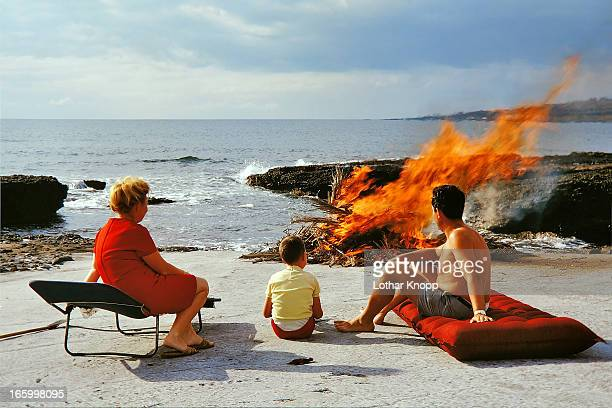 Family watching campfire burning down 1970