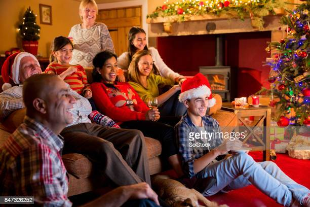 family watching christmas television - national holiday stock photos and pictures