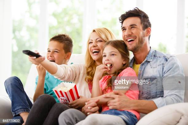 family watching funny movie together - family watching tv stock pictures, royalty-free photos & images