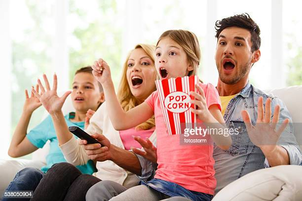 Family watching scary movie on TV