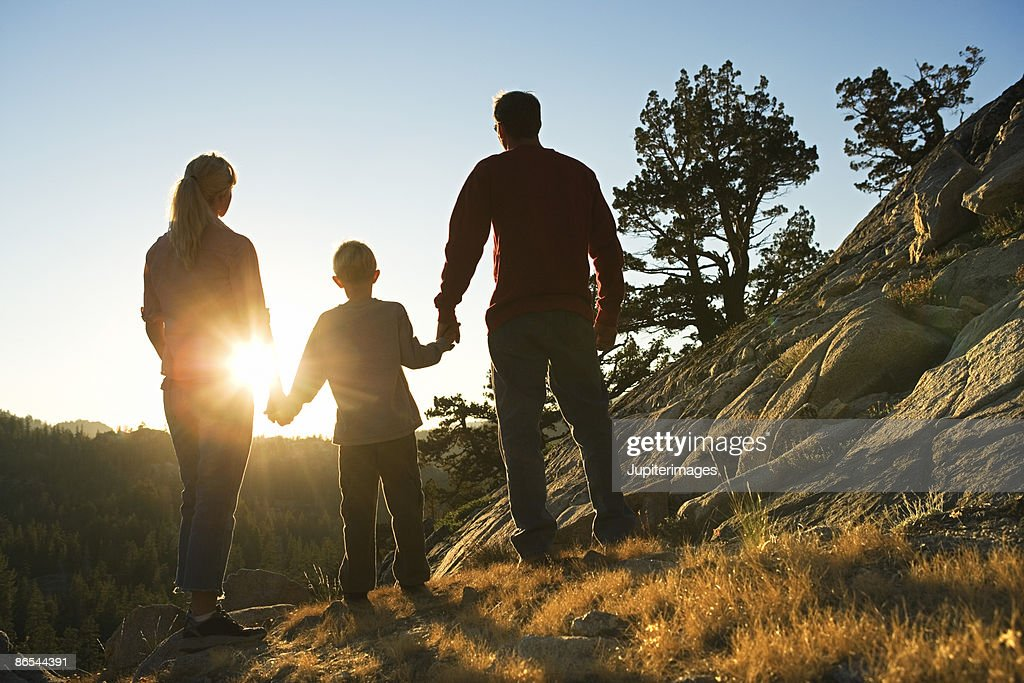 Family watching sunset : Bildbanksbilder