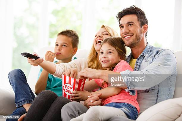 family watching television in living room - family watching tv stock pictures, royalty-free photos & images