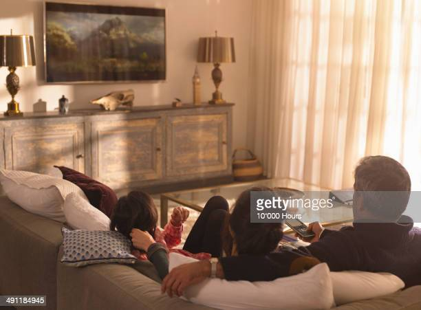 a family watching television - family watching tv stock pictures, royalty-free photos & images