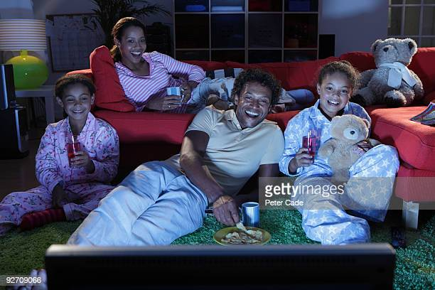 family watching television - family watching tv stock pictures, royalty-free photos & images