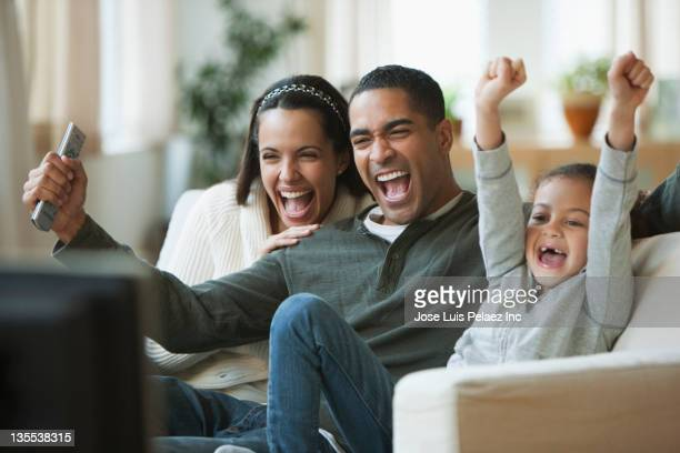 family watching television together - cheering ストックフォトと画像