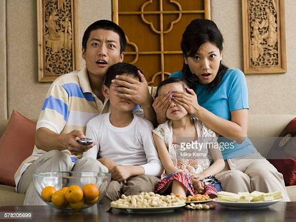 family watching television with parents covering childrens eyes - augen zuhalten stock-fotos und bilder