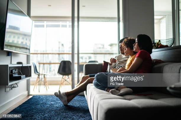 family watching tv and eating popcorn at home - film stock pictures, royalty-free photos & images