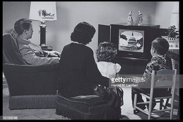 FAMILY WATCHING TV IN A LIVING ROOM SETTING