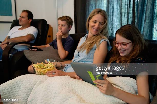 """family watching tv in living room, preteen girl on digital tablet. - """"martine doucet"""" or martinedoucet stock pictures, royalty-free photos & images"""