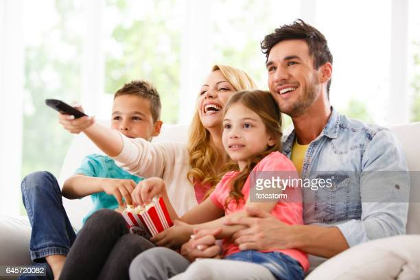 family watching tv on living room sofa - entertainment center stock pictures, royalty-free photos & images