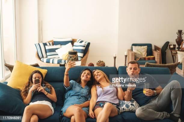 familie schaut zu hause auf dem sofa fern - mother daughter webcam stock-fotos und bilder