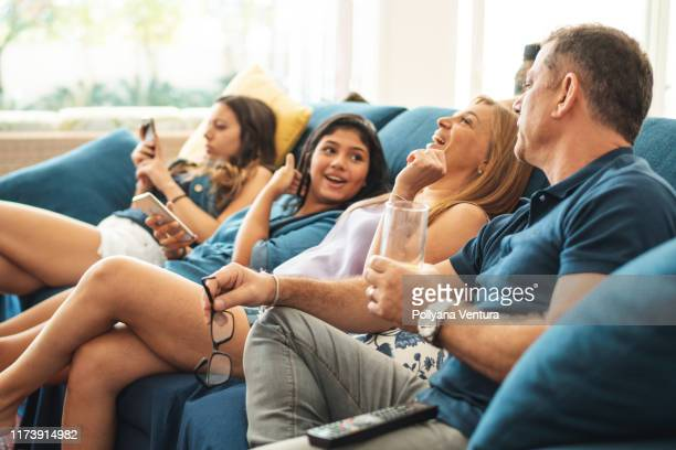 family watching tv - mid adult men stock pictures, royalty-free photos & images