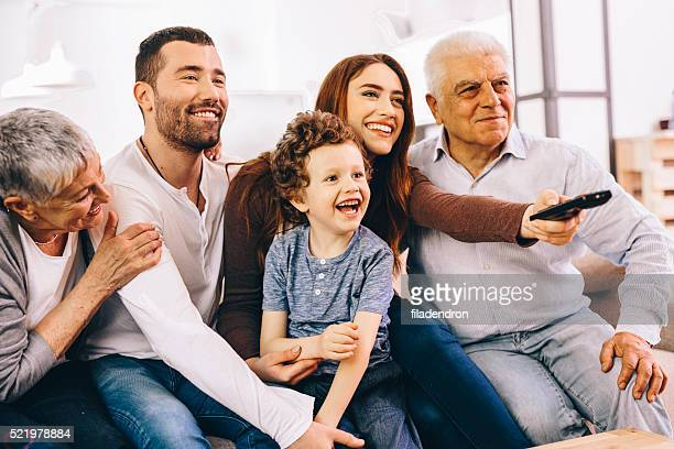 family watching tv - family watching tv stock pictures, royalty-free photos & images