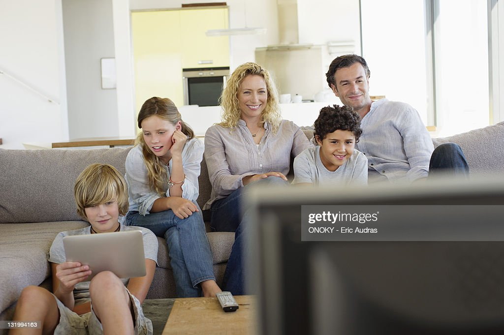 Family watching TV together at home : Stock Photo
