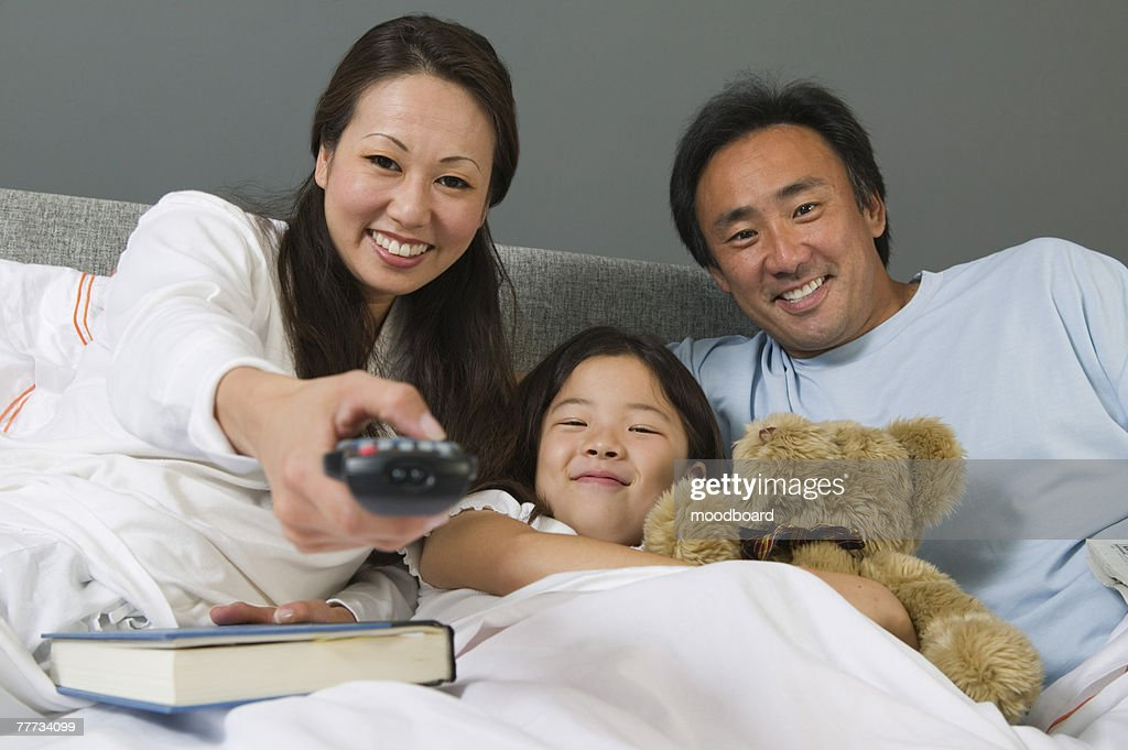 Family Watching TV Together in Bed : Stock Photo